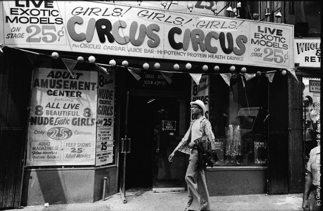 Exterior view of Circus Circus, an 'adult amusement center,' in Times Square as a man walks past wearing a hat and carrying his coat over his arm, New York, New York, 1970s. The marquee advertises exotic models, nude girls, books, magazines, games, and peep shows, as well as a juice bar and 'high-potency protein health drinks