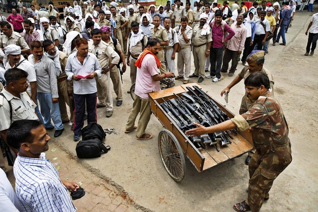 Weapons for police providing security for elections are handed out on the eve of the eighth phase of voting of Indian parliamentary elections in Allahabad, India, on May 6, 2014. (Photo by Rajesh Kumar Singh/Associated Press)