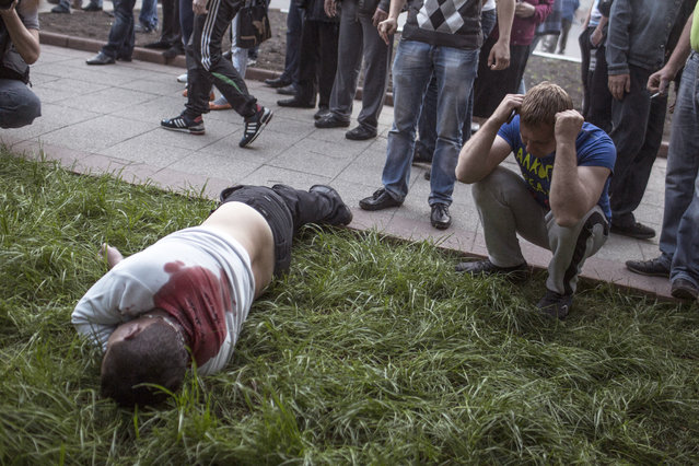 A man reacts next to the body of a pro-Russia man in Krasnoarmeisk, Ukraine, Sunday, May 11, 2014. (Photo by Manu Brabo/AP Photo)