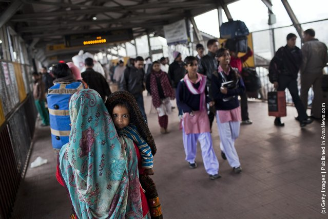 A woman carries a baby through  Nizamuddin Railway Station in New Delhi, India