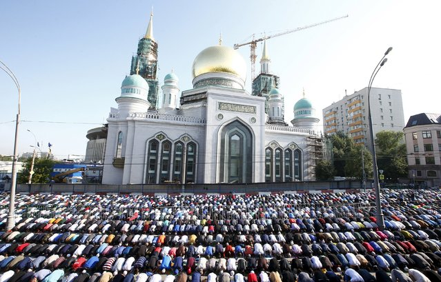 Muslims attend the morning prayers of Eid al-Fitr holiday, marking the end of the holy month of Ramadan, in Moscow, Russia, July 17, 2015. (Photo by Maxim Zmeyev/Reuters)