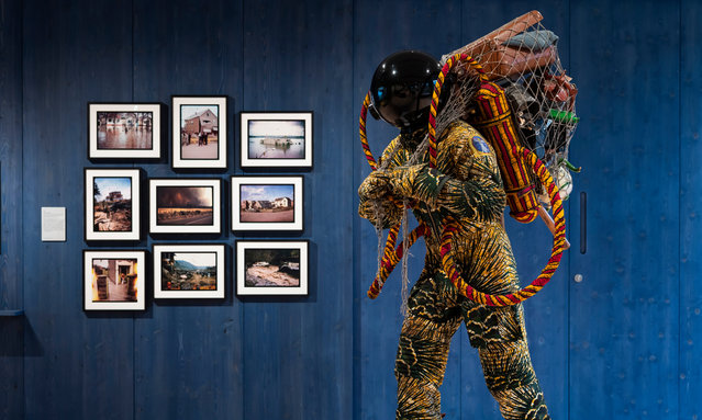 Refugee Astronaut III by Yinka Shonibare stands next to a series of photographs by Adam Chodzko at Wellcome Collection in London, England on September 03, 2019. This lifesize figure wears a suit made from a fabric reminiscent of traditional Nigerian textiles. Carrying a net of possessions, Shonibare's work invites visitors to create their own stories about who the figure might be, where they have come from and why they had to leave Earth in such a hurry. (Photo by Steven Pocock/Wellcome Collection)