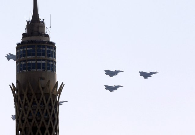 French-made Rafale fighter jets fly near Cairo Tower in central Cairo, Egypt, July 21, 2015. Dassault Aviation is raising Rafale fighter jet production in anticipation of further export orders, Chief Executive Eric Trappier said on Monday, as Egypt became the first country outside France to take delivery of the plane. (Photo by Reuters/Stringer)