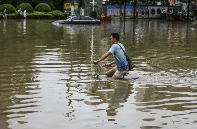A man rides his bicycle on a flooded street after heavy rainfall hit Wuhan, Hubei province, China, July 23, 2015. (Photo by Reuters/China Daily)