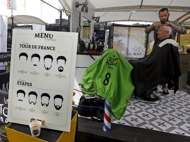 A barber shaves the head of Reuters photographer Stefano Rellandini at the hairdressing space of the Tour de France Village du depart (hospitality area) in Seranig, Belgium, July 7, 2015. (Photo by Eric Gaillard/Reuters)