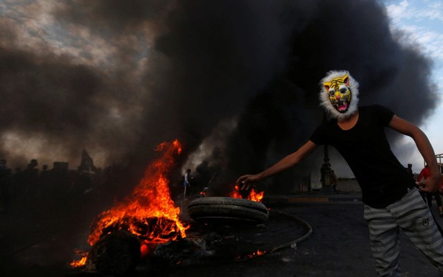 A masked protester throws a tire into fire during ongoing anti-government protests in Basra, Iraq on November 24, 2019. (Photo by Essam al-Sudani/Reuters)