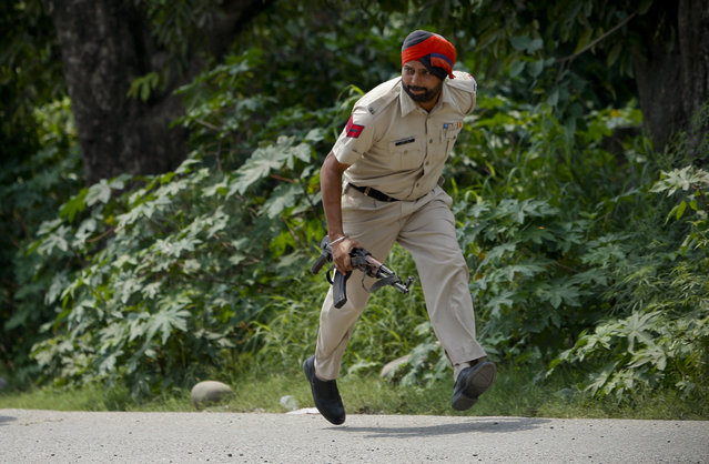 An Indian policeman takes position during a fight in the town of Dinanagar, in the northern state of Punjab, India, Monday, July 27, 2015. Indian army commandos joined police in fighting suspected militants who fired at a bus station and stormed into police barracks on the outskirts of a northern town bordering Pakistan early Monday. Rebels have been fighting for an independent Kashmir or its merger with Pakistan since 1989. (Photo by Channi Anand/AP Photo)