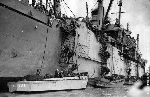 American troops climbing down guide nets into assault craft in preparation for the first great counter-strike of the Korean campaign
