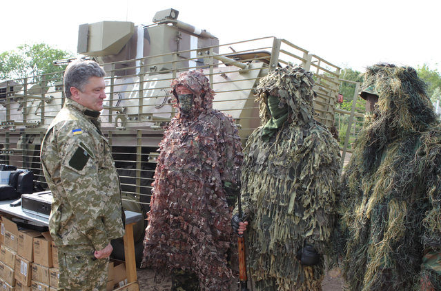 Ukrainian President Petro Poroshenko, left,  talks with the Ukrainian soldiers at a military base close to Slovyansk, in the Donetsk region, Ukraine, Friday, June 20, 2014. Clashes between government forces and pro-Russian separatist fighters flared ahead of the publication of a presidential peace plan that includes a unilateral cease-fire. (Photo by Mykhailo Markiv/AP Photo)
