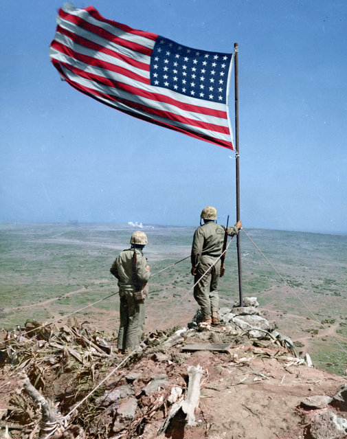 Two US Marines of the 4th Marine Division look over Iwo Jima from atop Mt. Suribachui, where, just two days before, the American flag was famously risen, February 25, 1945. (Photo by Jared Enos/Mediadrumworld.com)