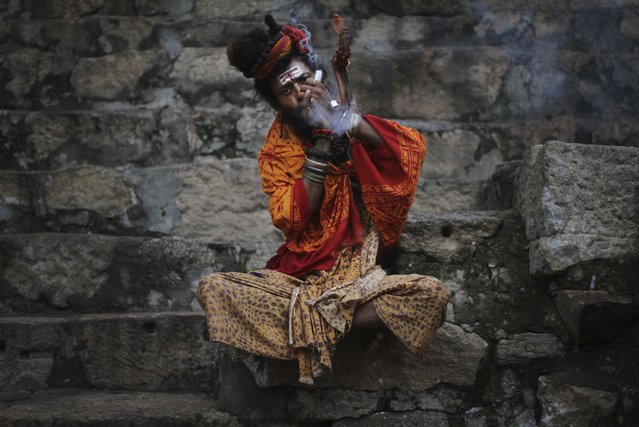 A Sadhu, or Hindu holy man, smokes marijuana at the Kamakhya temple in Gauhati, India, Saturday, June 21, 2014. The annual Ambubasi festival begins Sunday where hundreds of tantric Sadhus, holy men from an esoteric form of Hinduism, gather to perform rituals at the temple. (Photo by Anupam Nath/AP Photo)
