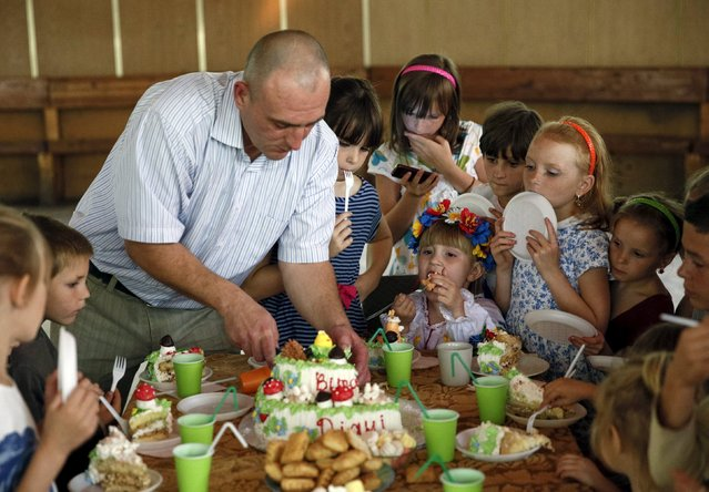 Children wait before taking a piece of a cake during a birthday party at a health and rest centre which serves as a temporary accommodation for refugees from eastern regions of the country in the town of Korostyshiv, Zhytomyr region, Ukraine, July 30, 2015. (Photo by Valentyn Ogirenko/Reuters)