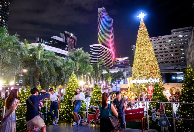 People enjoy the holiday season lights in downtown Bangkok on December 17, 2019. (Photo by Mladen Antonov/AFP Photo)