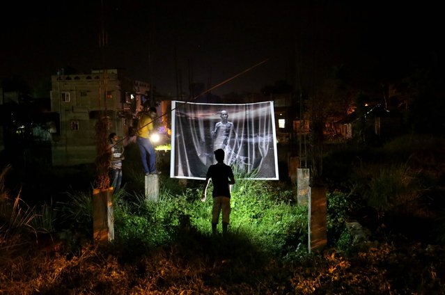 """Junior artists try to display an artwork at a constraction area as part of the """"People Art Festival"""" at Sarsuna Chander Haat in Calcutta, India, 10 June 2016. The 10-day-long international site spesific art festival with a title 'Migration' started on 01 June. (Photo by Piyal Adhikary/EPA)"""