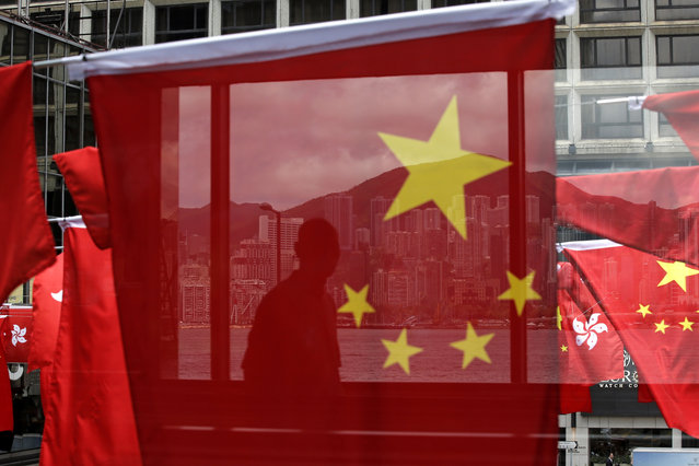 A man is reflected on a window as China and Kong Hong national flags are displayed outside a shopping center in Hong Kong Wednesday, June 28, 2017 to mark the 20th anniversary of Hong Kong handover to China. Hong Kong is planning a big party as it marks 20 years under Chinese rule. But many people in the former British colony are not in the mood to celebrate. (Photo by Kin Cheung/AP Photo)