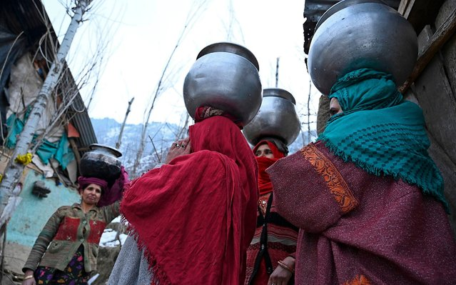 Women carry water pitchers on their head after a water pipe got frozen due to sub zero temperatures on the outskirts of Srinagar on January 3, 2020. (Photo by Tauseef Mustafa/AFP Photo)