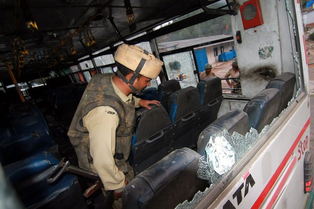 An Indian paramilitary force soldier inspects the bus in which a militant was travelling and opened fire at security personnel at a checkpost on Jammu-Srinagar National highway at Kud, some 90 km from Jammu, the winter capital of Kashmir, India, 13 June 2016. A militant and a civilian were killed and three security personnel critically injured after suspected terrorists attacked at Central Reserve Police Force (CRPF) camp Kudh on the Jammu-Srinagar national highway in Jammu region. (Photo by Jaipal Singh/EPA)