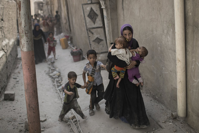 Iraqi civilians flee through an alley as Iraqi Special Forces continue their advance against Islamic State militants in the Old City of Mosul, Iraq, Monday, July 3, 2017. (Photo by Felipe Dana/AP Photo)