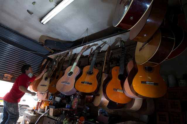 Ecuadorian luthier Ivan Ibujes hangs a guitar after repairing it at his shop in Quito June 17, 2016. (Photo by Guillermo Granja/Reuters)