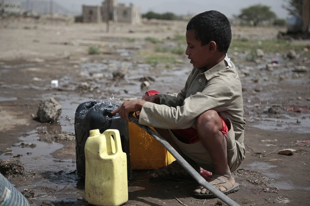 A boy fills a container with water from a well that is allegedly contaminated with cholera bacteria, on the outskirts of Sanaa, Yemen, Wednesday, July 12, 2017. The U.N. health agency said Tuesday that plans to ship cholera vaccine to Yemen are likely to be shelved over security, access and logistical challenges in the war-torn country. Yemen's suspected cholera caseload has surged past 313,000, causing over 1,700 deaths in the world's largest outbreak. (Photo by Hani Mohammed/AP Photo)
