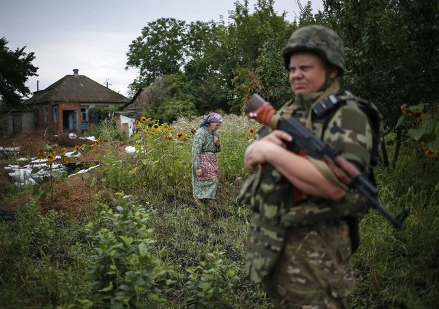 """A member of the Ukrainian police special task force """"Kiev-1"""" patrols in the eastern Ukrainian village of Semenovka near Sloviansk, July 14, 2014. Ukraine on Monday accused Russian army officers of fighting alongside separatists in the east of the country and said Moscow was once more building up its troops on the joint border. (Photo by Gleb Garanich/Reuters)"""