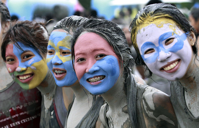 Women have their face applied color mud during the Boryeong Mud Festival at Daecheon Beach in Boryeong, South Korea, Friday, July 18, 2014. The annual mud festival features mud wrestling and mud sliding. (Photo by Ahn Young-joon/AP Photo)
