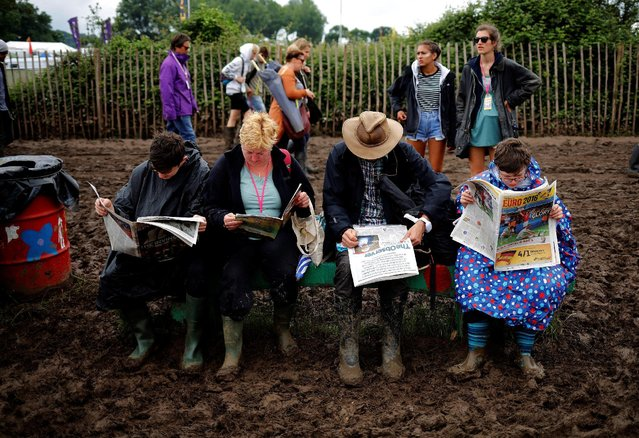 Revellers read newspapers at Worthy Farm in Somerset during the Glastonbury Festival, Britain, June 26, 2016. (Photo by Stoyan Nenov/Reuters)