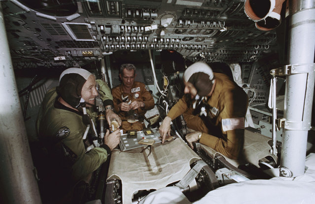 Three ASTP crewmen have a meal in the Apollo Command Module trainer in Building 35 during Apollo-Soyuz Test Project joint crew training at NASA's Johnson Space Center, on February 25, 1975. They are, left to right, cosmonaut Aleksey A. Leonov, commander of the Soviet ASTP first (prime) crew; astronaut Donald K. Slayton, docking module pilot of the American ASTP prime crew; and astronaut Thomas P. Stafford, commander of the American ASTP prime crew. (Photo by NASA)