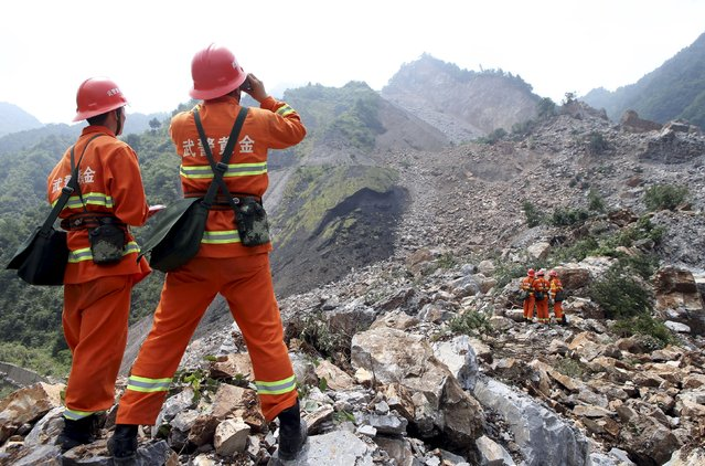 Rescue workers search for survivors at the site of a landslide which hit a mining factory on Wednesday in Shanyang county, Shaanxi province, China, August 13, 2015. A total of 65 people remained missing after a landslide buried over 15 dormitories and three houses which belong to a mining company in northwest China's Shaanxi Province, local authorities confirmed on Thursday, Xinhua News Agency reported. (Photo by Reuters/China Daily)