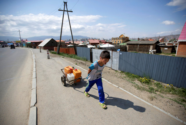 A boy carries water along a road in Ulan Bator, Mongolia, June 27, 2016. (Photo by Jason Lee/Reuters)