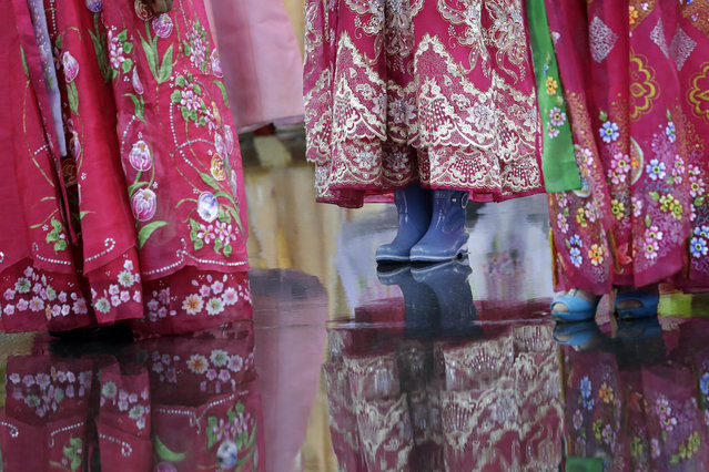 A university student wears a pair of rain boots with her traditional Korean dress as she waits in the rain for the start of a mass dance on Thursday, July 27, 2017, in Pyongyang, North Korea as part of celebrations for the 64th anniversary of the armistice that ended the Korean War. (Photo by Wong Maye-E/AP Photo)