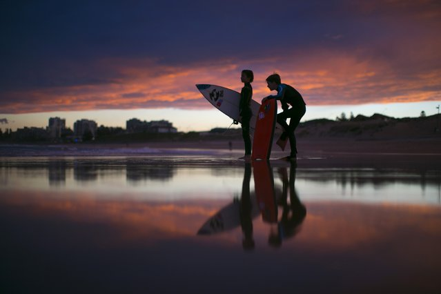 """Young surfers, nicknamed """"grommets"""" in local surfing parlance, wait for their friends to finish a post-sunset session on the waves off Wanda Beach in Sydney, July 16, 2014. Many of Sydney's famed beaches remain popular with surfers during the southern hemisphere winter months despite early sunsets and cooler ocean temperatures. (Photo by Jason Reed/Reuters)"""