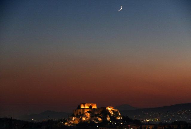 A waxing crescent moon rises over the lit Temple of Parthenon atop the ancient Acropolis hill in central Athens, Greece July 25, 2017. (Photo by Yannis Behrakis/Reuters)