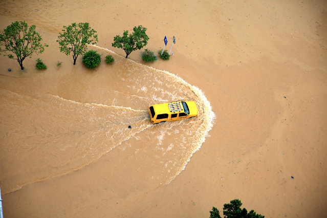 An automobile is seen passing a flooded street in Rongjiang, Guizhou Province, China, July 2, 2016. (Photo by Reuters/Stringer)