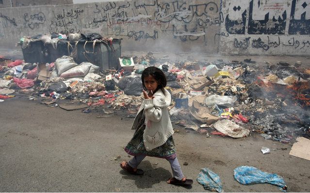 A Yemeni girl gestures while passing through a pile of garbage in the streets of Sanaa (Yemen), after garbage collectors completed their fifth day of strike in protest over pay on July 10, 2012