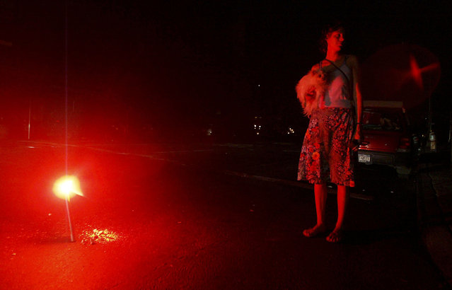 A woman holds her dog whilst she stands next to a flare during a massive blackout August 15, 2003 in New York City. Power is slowly returning to certain parts of the city. (Photo by Mario Tama/Getty Images)