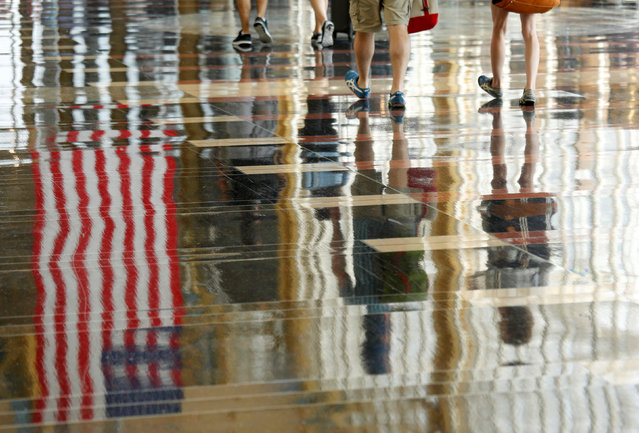 A U.S. flag is reflected on the floor as passengers make their way through Reagan National Airport at the start of the Independence Day holiday weekend in Washington, U.S., July 1, 2016. (Photo by Kevin Lamarque/Reuters)