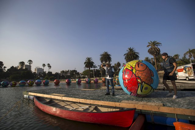 "Volunteers wait to load an inflated sphere into a canoe to be lowered in MacArthur Park Lake during the installation of Portraits of Hope's exhibition ""Spheres at MacArthur Park"" in Los Angeles, California August 21, 2015. (Photo by Mario Anzuoni/Reuters)"