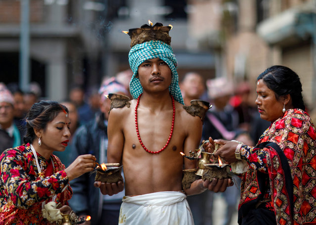 Devotees with lit oil lamps perform religious rituals during the Swasthani Brata Katha festival at Thecho in Lalitpur, Nepal, February 6, 2020. (Photo by Navesh Chitrakar/Reuters)