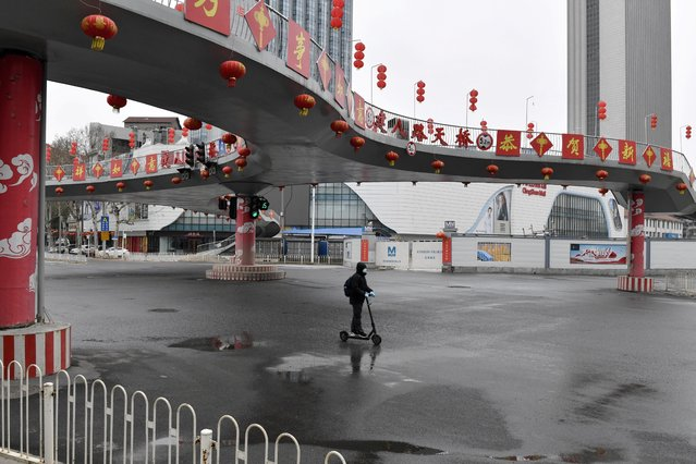 A man wearing a face mask rides a kick scooter through an empty intersection in Wuhan, China on March 3, 2020. (Photo by Reuters/China Stringer Network)