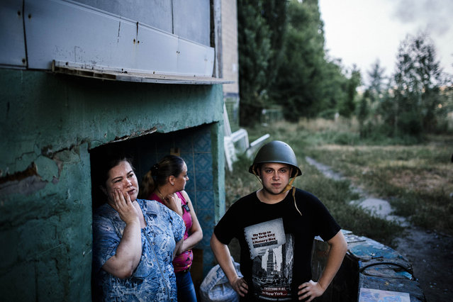 "People stand at the entrance of a makeshift bomb shelter in Donetsk, on August 10, 2014. Artillery pounded the surrounded main rebel bastion of Donetsk in east Ukraine Sunday as the West warned Russia that any attempt to send ""humanitarian"" troops into the conflict-torn region would be deemed ""unacceptable"". (Photo by Dimitar Dilkoff/AFP Photo)"