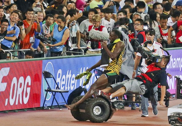 Usian Bolt of Jamaica is hit by a cameraman on a Segway as he celebrates after winning the men's 200 metres final at the 15th IAAF World Championships at the National Stadium in Beijing, China, August 27, 2015. (Photo by Reuters/Stringer)