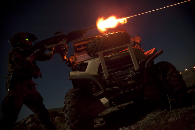 A Marine Special Operations Team member fires a M240B machine gun during night fire sustainment training in Helmand province, Afghanistan, March 28, 2013. Marine Special Operations Team members are deployed in Helmand province to train and mentor Afghan National Security Forces. (Photo by Sgt. Pete Thibodeau/U.S. Marine Corps photo)