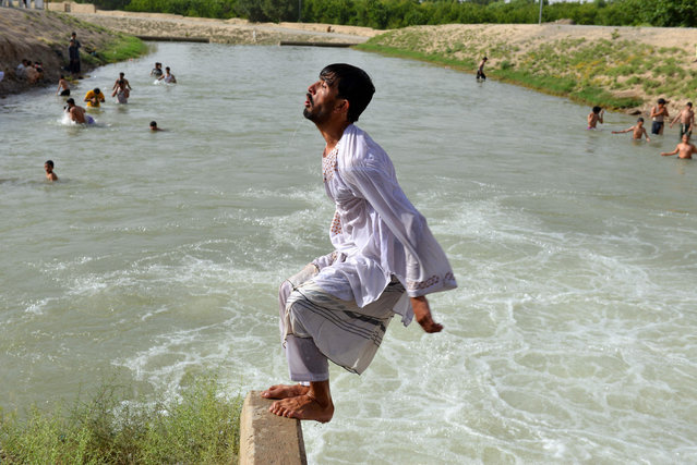 Afghan youth swimming in a canal during the Islamic holy month of Ramadan in Kandahar on June 23, 2016. Muslims throughout the world are marking the month of Ramadan, the holiest month in the Islamic calendar during which devotees fast from dawn till dusk. (Photo by Jawed Tanveer/AFP Photo)