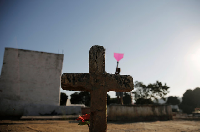 A boy helps his friend (unseen) to fly a kite in a cemetery in the Vila Operaria Favela of Rio de Janeiro, Brazil, July 10, 2016. (Photo by Nacho Doce/Reuters)