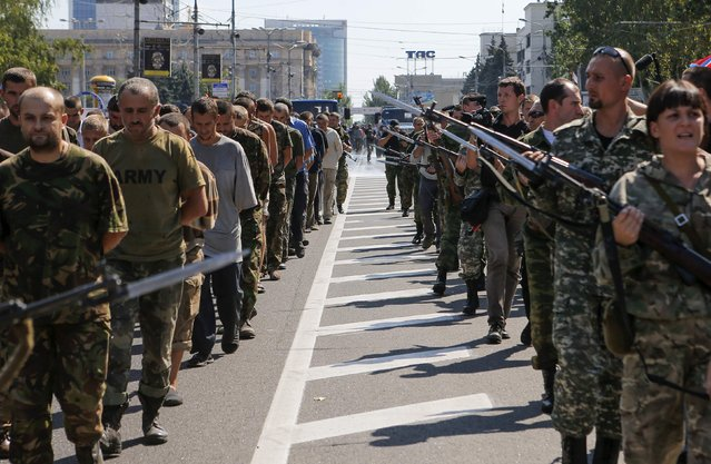 Armed pro-Russian separatists (R) escort a column of Ukrainian prisoners of war as they walk across the centre of Donetsk August 24, 2014. Pro-Russian separatist rebels force-marched dozens of Ukrainian prisoners of war along the main street of the rebel-held Ukrainian town of Donetsk on Sunday. (Photo by Maxim Shemetov/Reuters)