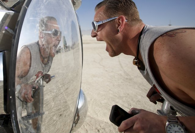"""Wilf Griese interacts with the art installation Compound Eye during the Burning Man 2015 """"Carnival of Mirrors"""" arts and music festival in the Black Rock Desert of Nevada, August 31, 2015. (Photo by Jim Urquhart/Reuters)"""