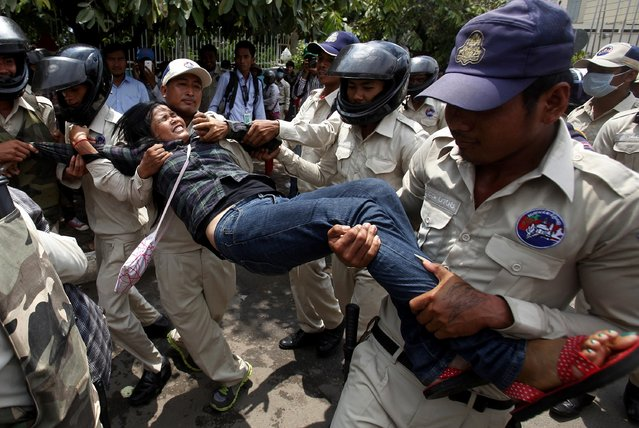 Cambodian security officers carry a woman during a protest near the National Assembly in Phnom Penh August 27, 2014. Boeung Kak lake residents and other communities who are embroiled in land disputes gathered near the National Assembly to appeal for help from the government. (Photo by Samrang Pring/Reuters)