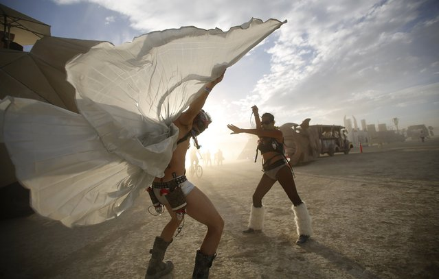 "Dillon Bracken (L) and Atalya Stachel dance during the Burning Man 2014 ""Caravansary"" arts and music festival in the Black Rock Desert of Nevada, August 30, 2014. Over 65,000 people from all over the world have gathered at the sold out festival to spend a week in the remote desert cut off from much of the outside world to experience art, music and the unique community that develops. (Photo by Jim Urquhart/Reuters)"