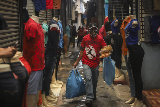 A man, wearing a protective face mask, walks through a popular market in Managua, Nicaragua, Tuesday, April 7, 2020. Restaurants are empty, there's little traffic in the streets and beach tourists are sparse headed into Holy Week despite the government's encouragement for Nicaraguans to go about their normal lives. (Photo by Alfredo Zuniga/AP Photo)